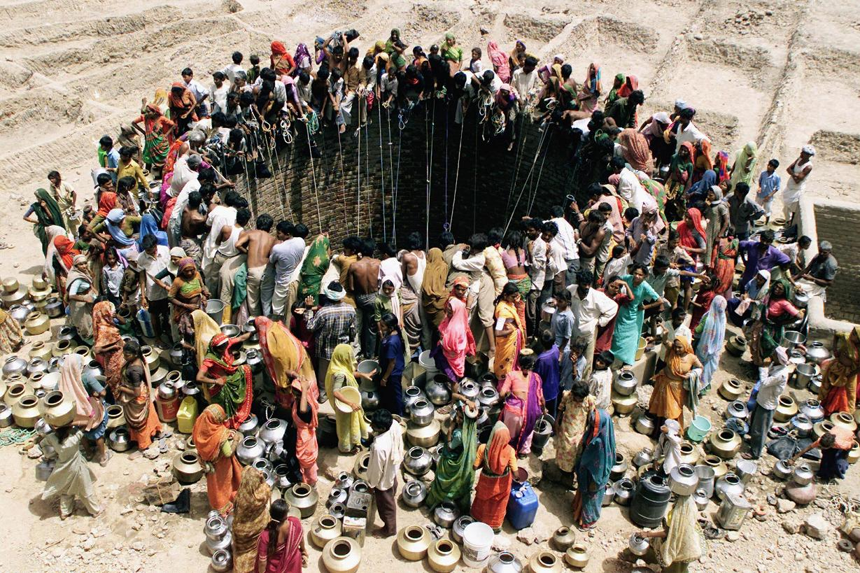 People gather to get water from a huge well in the village of Natwarghad in the western Indian state of Gujarat